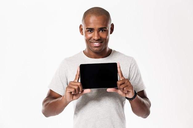 Happy african man showing blank tablet computer screen and looking