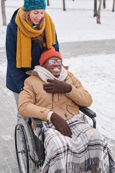 Счастливый африканский мужчина сидит в инвалидной коляске и наслаждается прогулкой с другом на свежем воздухе зимой