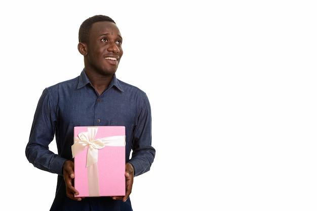 考えながら笑顔とギフトボックスを保持している幸せなアフリカ人