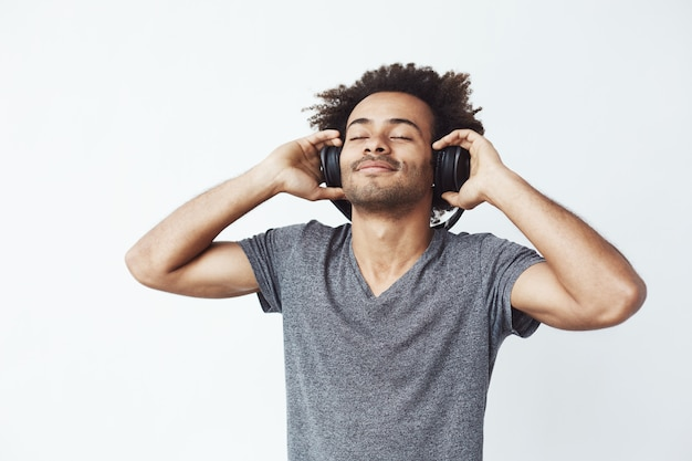 Happy african man smiling listening to music in headphones.