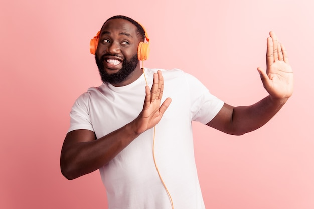 Счастливый африканский мужчина улыбается, слушая музыку в наушниках, избегая показывать руки