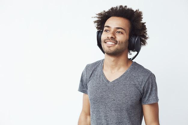 Прослушивание счастливого африканского человека усмехаясь к музыке в наушниках.