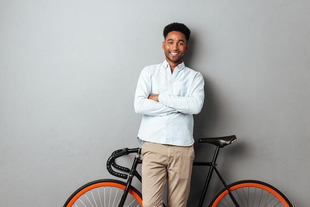 自転車の近くに立って幸せなアフリカ人