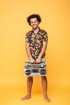 Uomo africano felice che sta con il registratore