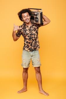 Счастливый африканский человек стоя с магнитофоном