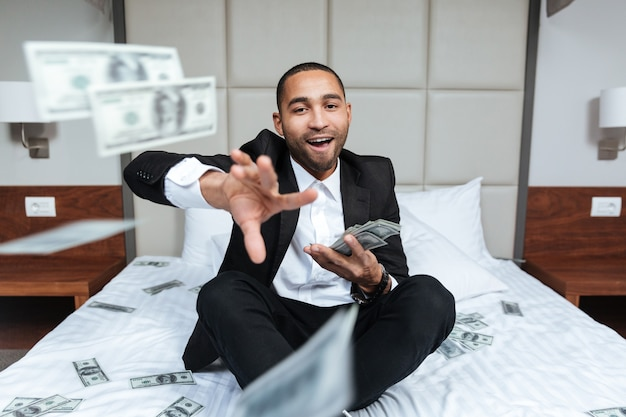 Happy african man in suit throws the money and sitting on bed in hotel room