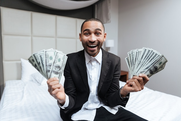 Happy african man in suit with money in hands sitting on bed with open mouth in hotel room