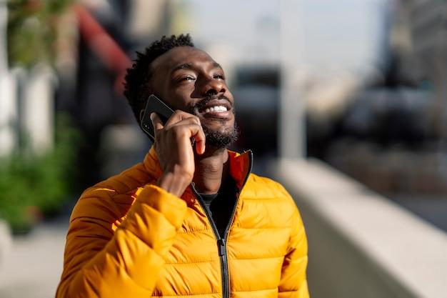 焦点の合っていない背景を持つ街を歩いている携帯電話で話している幸せなアフリカ人