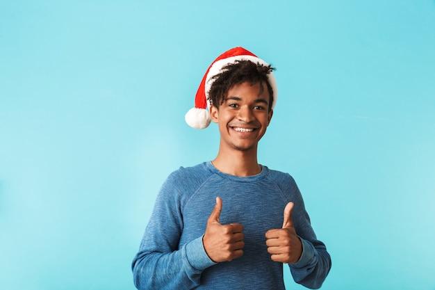 青い壁に隔離されたクリスマスの赤い帽子をかぶって、親指をあきらめて幸せなアフリカ人