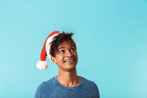 青い壁に隔離されたクリスマスの赤い帽子をかぶって、目をそらして幸せなアフリカ人