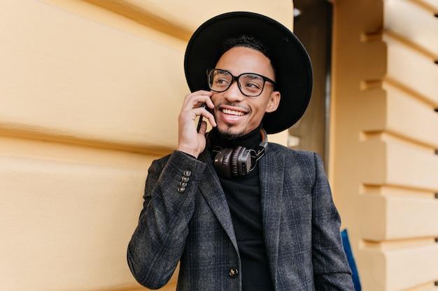 친구를 호출하고 웃고 큰 눈을 가진 행복 한 아프리카 사람. 전화와 노란색 벽 근처에 서 유행 회색 옷차림에 남자의 야외 사진.