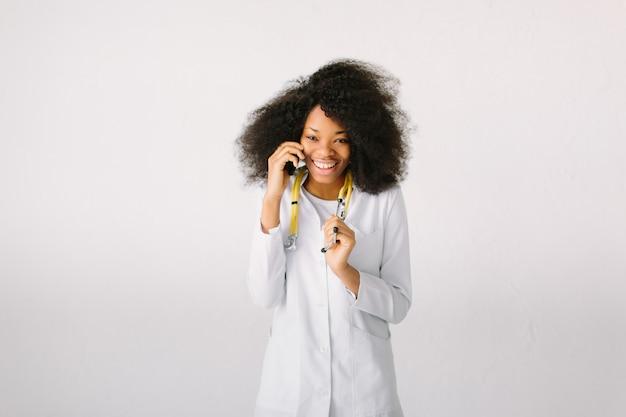 흰색 배경에 병원에서 청진 기 스튜디오에서 행복 아프리카 의료 인턴 의사와 전화 통화