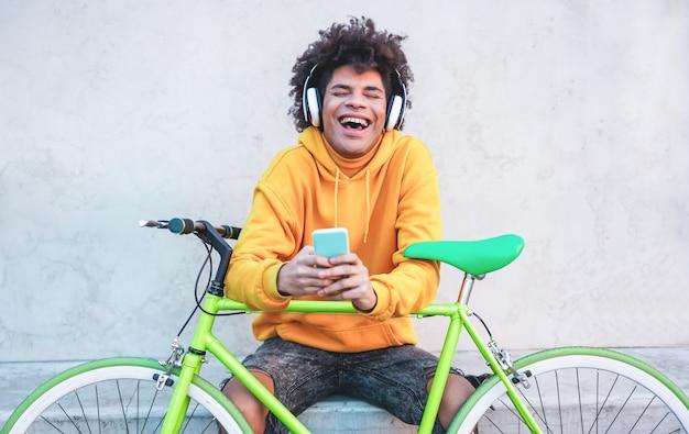 屋外のスマートフォンアプリで音楽プレイリストを聞いて幸せなアフリカの千年の男-技術トレンドを楽しんでいる若い男-技術、世代z、スタイリッシュなコンセプト-顔に焦点を当てる