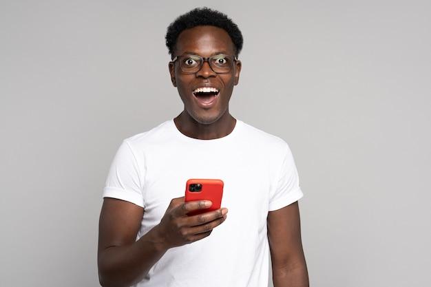 眼鏡をかけた幸せなアフリカのミレニアル世代の男性は、スタジオの灰色の背景で隔離の携帯電話を保持している白いtシャツを着ています。赤いケースのスマートフォンを使用して、カメラを見て、広く笑っている黒人の男。