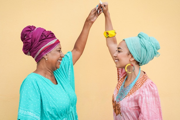 Happy african mother and daughter dancing while wearing traditional dresses - focus on faces