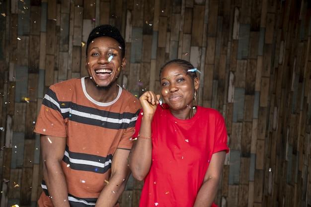 Felici africani che festeggiano con i coriandoli davanti a una parete di legno