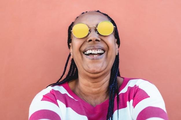 街で屋外で自分撮りをしている幸せなアフリカの年配の女性-顔に焦点を当てる