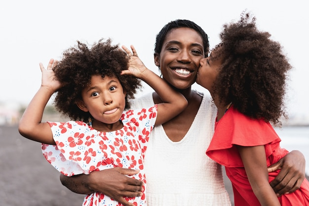 Happy african sister twins kissing mother on the beach - focus on mother face