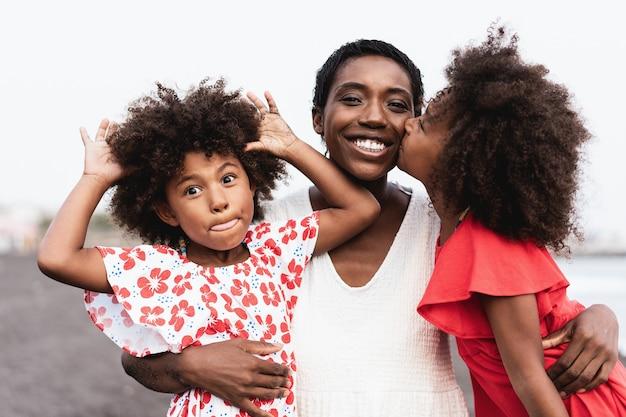 ビーチで母親にキスする幸せなアフリカの姉妹双子-母親の顔に焦点を当てる