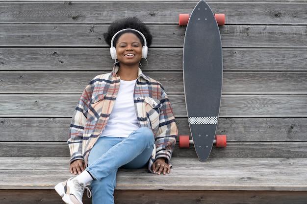 스케이트보드를 탄 행복한 아프리카 스케이트보더 소녀는 도시 우주 공원에서 야외에서 편안한 음악을 듣습니다.