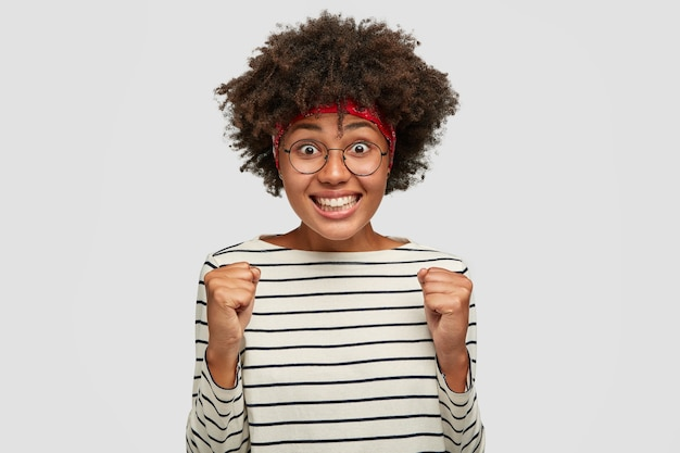 행복한 아프리카 학생은 승자처럼 느끼고, 승리에 주먹을 쥐고, 모든 시험을 성공적으로 통과하게되어 기쁩니다.