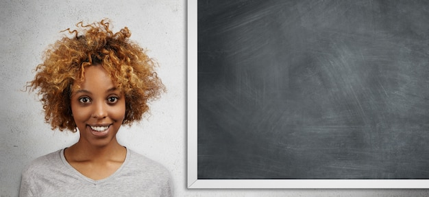 Happy african student with afro hairstyle standing isolated against blank chalkboard with copy space for your advertising content with joyful expression, getting a at math class