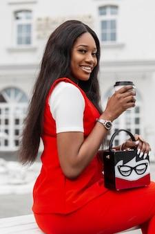 ファッショナブルな赤いスーツのかわいい笑顔で幸せなアフリカのスタイリッシュな若い女性は、通りでコーヒーを飲みます。ヴィンテージのハンドバッグと若者の流行の服を着た上質な黒人の女の子は、街の建物の近くのベンチに座っています。