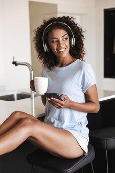 携帯電話を使用してヘッドフォンで幸せなアフリカの女性
