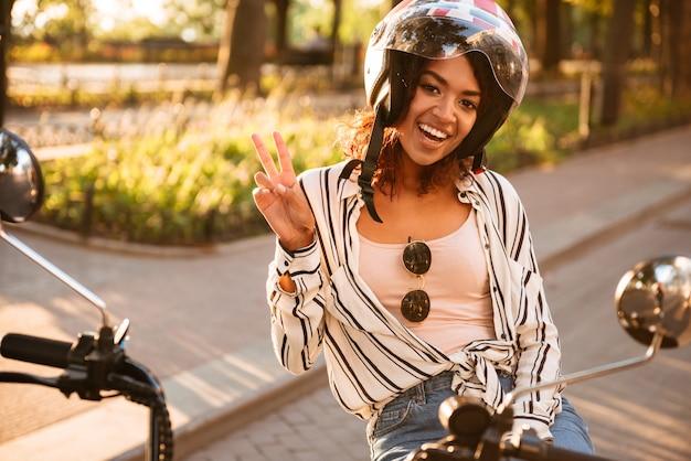 現代のバイクを屋外に座って見ているとカメラで平和を見せながらモトヘルメットで幸せなアフリカの女