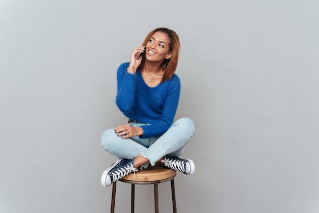 스웨터와 청바지를 입은 행복한 아프리카 여성이 의자에 앉아 전화 통화를 합니다. 격리 된 회색 배경