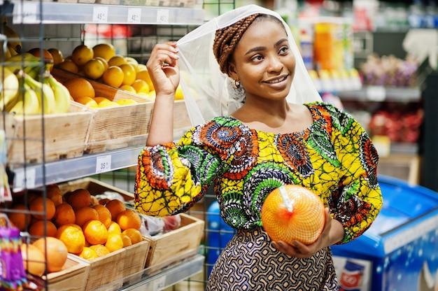 スーパーで買い物、伝統的な服や食料品店でベールを探して製品の幸せなアフリカの女性。市場で果物を買うアフロ黒人女性の衣装。