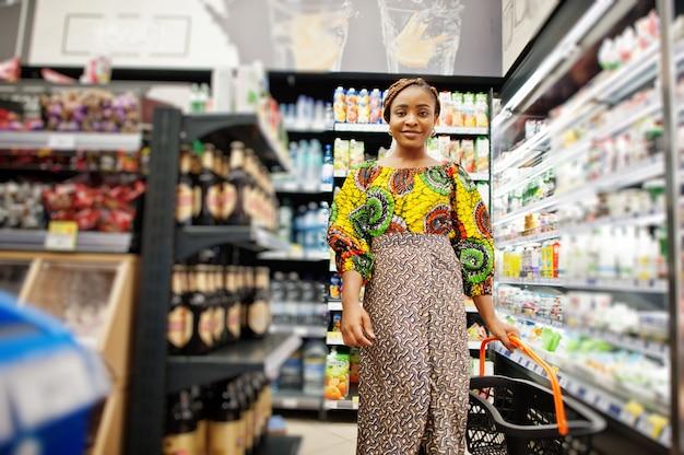 スーパーで買い物、伝統的な服や食料品店でベールを探して製品の幸せなアフリカの女性。市場で買い物をするバスケットを持つアフロ黒人女性の衣装。