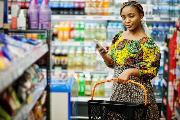 スーパーで買い物、伝統的な服や食料品店でベールを探して製品の幸せなアフリカの女性。携帯電話を持つアフロの黒人女性。