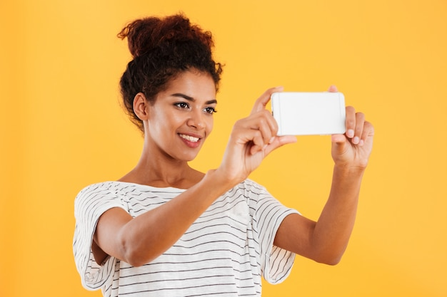 Happy african woman making photo on phone