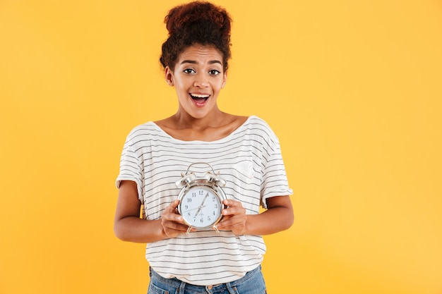 Happy african woman rejoice while holding alarm clock