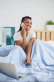 Happy African woman talking on phone in bedroom