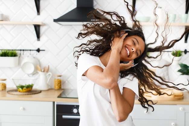 Happy african woman twirls her hair and listens to music via headphones in the kitchen