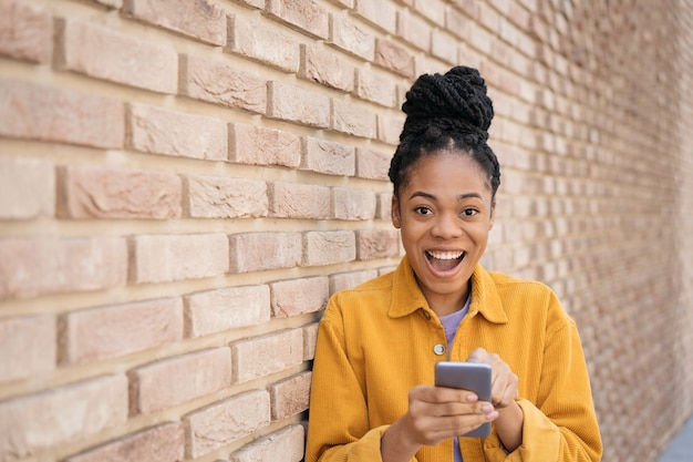 Happy african woman using mobile app shopping online with sales inspiration black friday concept