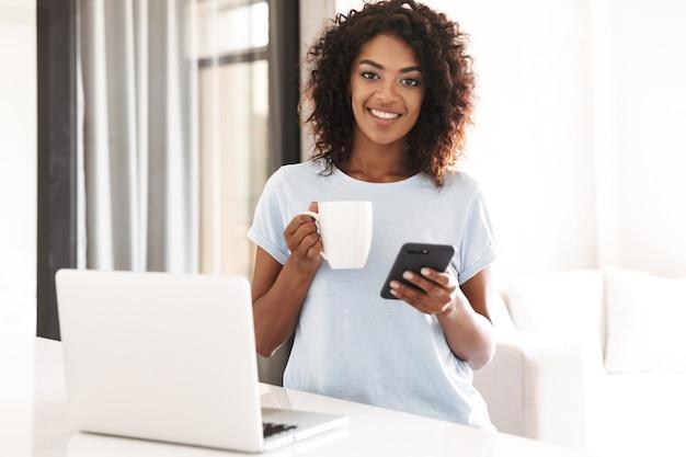 携帯電話を使用して幸せなアフリカの女性