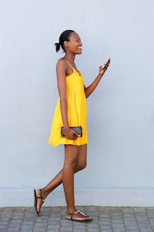 Happy african woman walking and using mobile phone