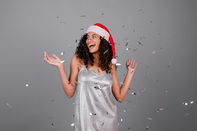Happy african woman wearing christmas hat with silver confetti in the air isolated over grey