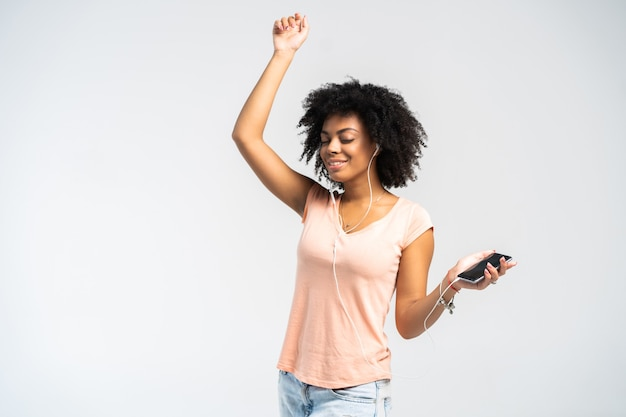 彼女が彼女の電話から聞いている音楽に合わせて踊るアフロとカジュアルな服を着た幸せなアフリカの女性。