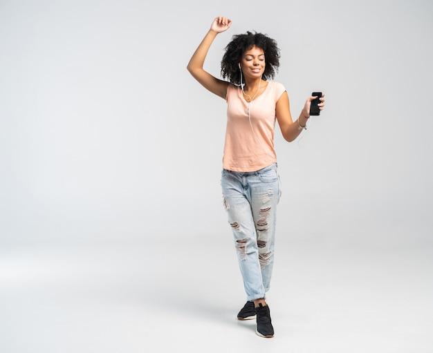 아프리카와 캐주얼 의류 그녀가 그녀의 전화에서 듣고 음악에 맞춰 춤을 행복 아프리카 여자.