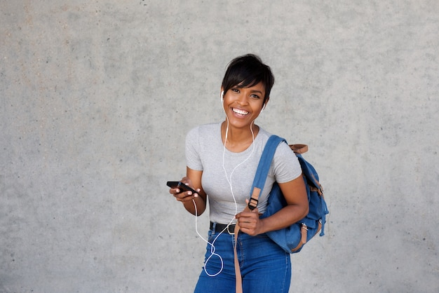 Happy african woman with bag listening music on mobile against gray wall
