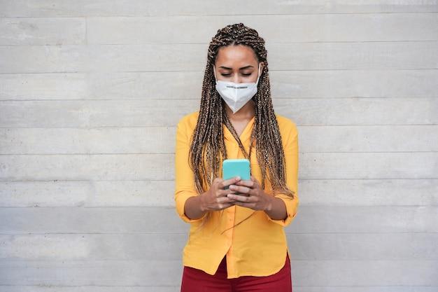 Счастливая африканская женщина с защитной маской для лица с помощью мобильного телефона на открытом воздухе - фокус на лице