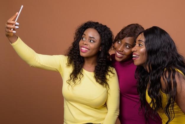 携帯電話でselfieを取って幸せなアフリカの女性