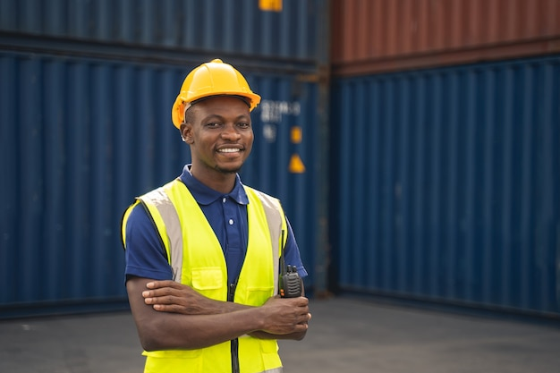 Happy african worker smailing, standing in the container workplace and crossed arms with feeling happiness