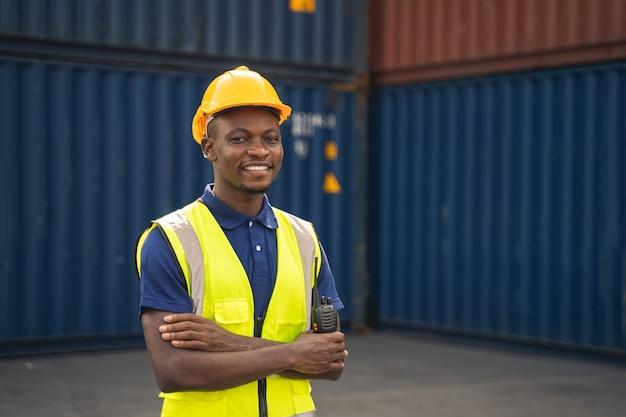 Счастливый африканский рабочий улыбается, стоит на рабочем месте контейнера и скрещивает руки от счастья
