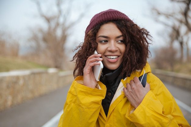 Happy african young lady wearing yellow coat talking by phone.