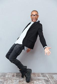 ダンスと笑顔のメガネで幸せなアフリカの若い男